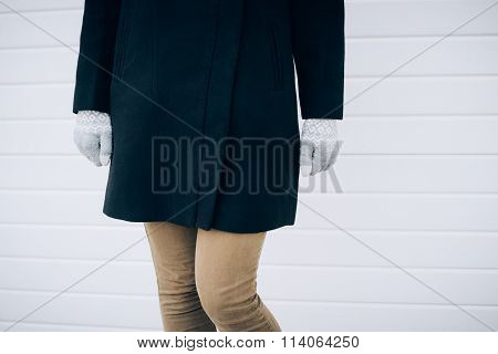 Girl In Black Coat, Beige Jeans And Gray Gloves Standing On White Background