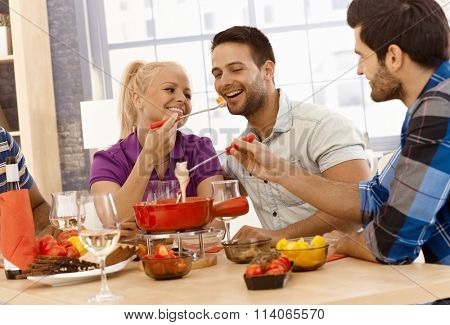 Happy couple having cheese fondue with friends, smiling.