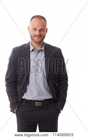 Portrait of confident businessman standing hands in pockets, smiling, looking at camera.