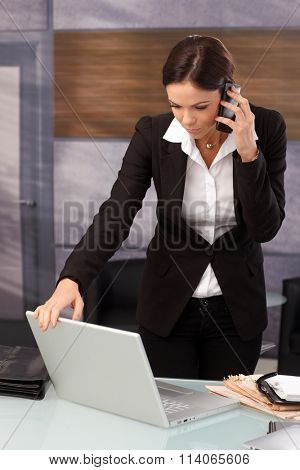 Young businesswoman standing at desk opening laptop, talking on mobilephone.