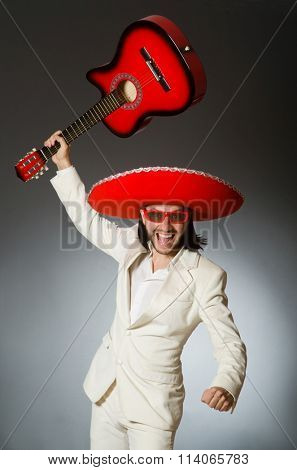 Funny mexican in suit holding guitar against gray