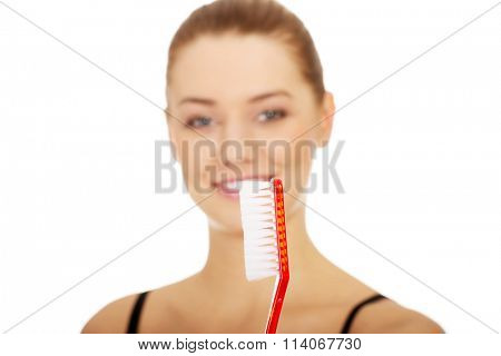 Woman with oversized toothbrush.
