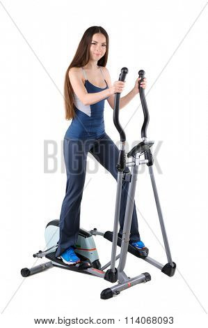 young woman doing exercises on elliptical trainer