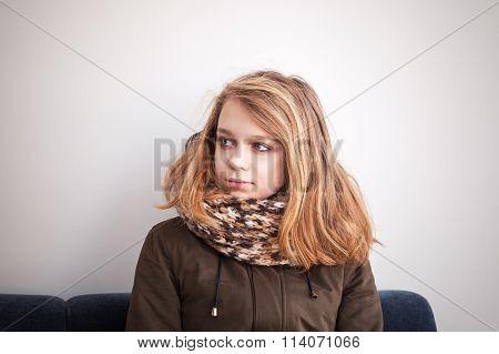 Teenage Girl In Warm Outwear Sitting On Blue Sofa