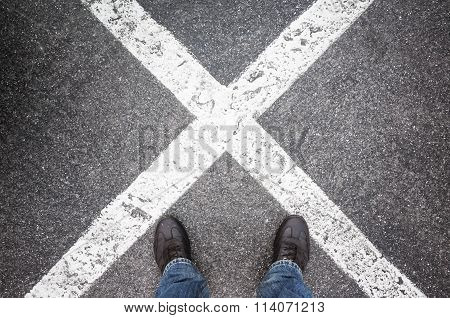 Feet Standing On Dark Urban Asphalt With Crossing Lines