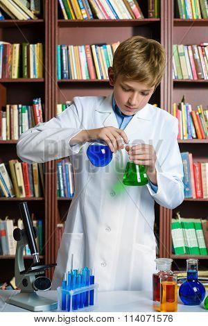 Cute boy doing biochemistry research in chemistry class