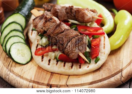 Grilled meat skewer served with salad over pita bread