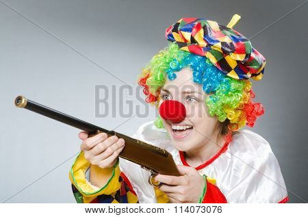 Clown with rifle isolated on white