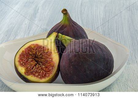 Figs whole and a half in a white bowl