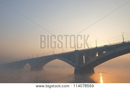 Communal Bridge at sunset in the mist over the river