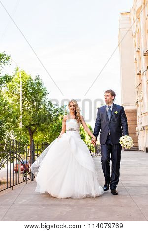 Bride and groom walking away in summer park outdoors