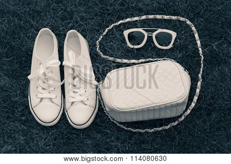 Purse, Sneakers And Sunglasses With  Grass As A Background