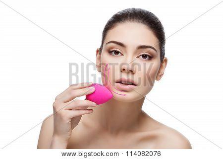 Beautiful girl applying foundation with sponge