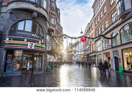 Copenhagen Square with shops and walking people, christmas decorations on December 21, 2014