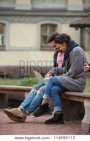 Happy couple surfing the Internet in the city