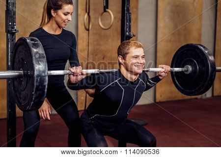 Closeup man and personal trainer with barbell