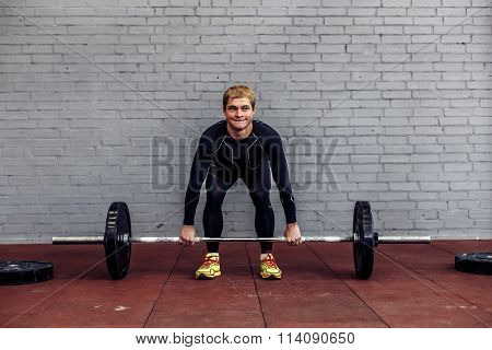 Young man doing deadlift exercise at gym