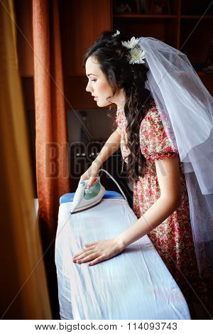 The bride preparing for wedding ceremony, ironing her gown on board, natural light. She is dressed i