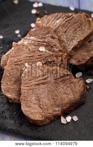 Sliced roast beef on a slate cutting board