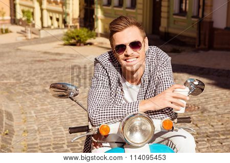 Smiling Man In Spectacles Sitting On The Bike And Holding Coffee