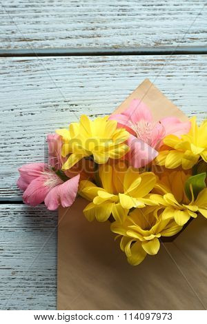 Pink alstroemeria and yellow chrysanthemum in envelope on wooden background