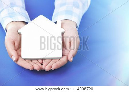 Female hands holding house on blue background