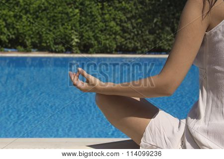 Woman meditating at the edge of a swimming pool