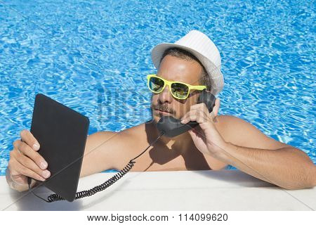 Guy having an internet call from the swimming pool