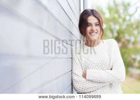 Beautiful natural young smiling brunette woman wearing knitted sweater by the house. Fall and winter fashion concept.