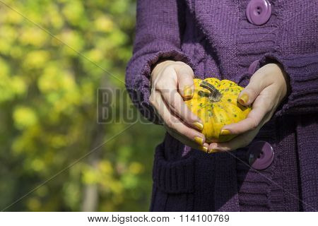 Female holding yellow gourd in the woods