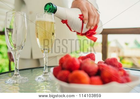 groom pouring champagne into a glass in the open air. in the foreground a saucer with strawberry