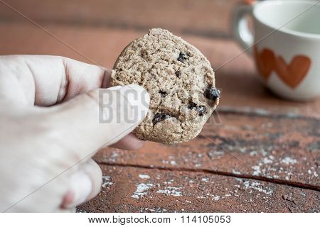 Woman's Hand Holding Up A Chocolate Cookies. Valentine's Day Background.