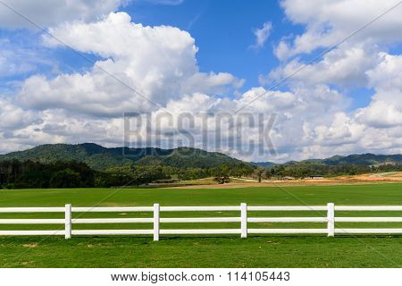 Green Meadow With Blue Sky And White Fence