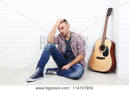 Young musician with guitar on light wall background