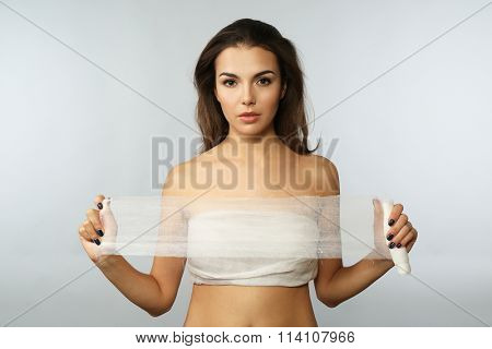 Young beautiful woman with a bandage on her chest, holding gauze, on grey background