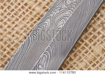 Fragment of the traditional handmade Finnish knife blade with the wave pattern of damascus steel.