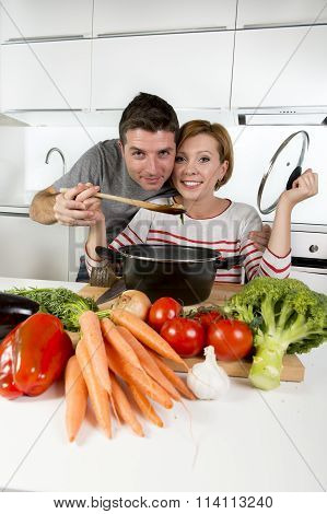 American Couple At Home Kitchen Smiling Happy Together Wife Cooking Husband Tasting The Vegetable St