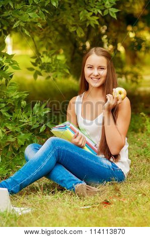 Girl student with books eating an apple