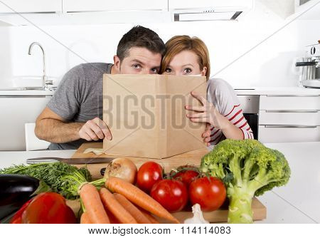 American Couple Working In Domestic Kitchen Following Recipe Reading Cookbook Together