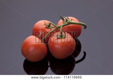 Tomatoes On Shiny Black Background.