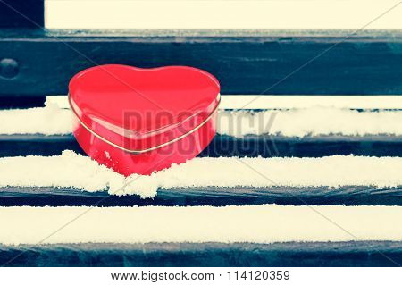Red Heart Shaped Tin Box On A Bench Covered With Snow