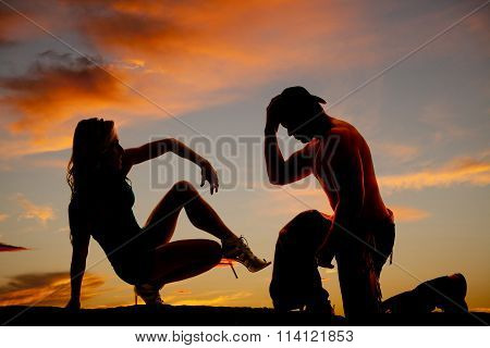 Silhouette Of Cowboy On Knee And Woman Sit Back One Leg Up In The Sunset