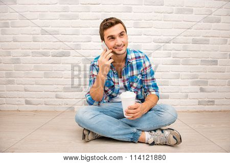 Handsome Man Sitting On The Floor With Crossed Legs And Holding Phone