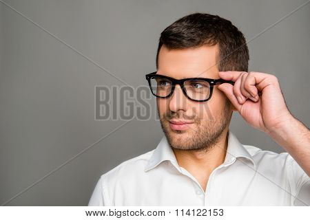 Smart Man  Touching His Glasses And Looking Ahead