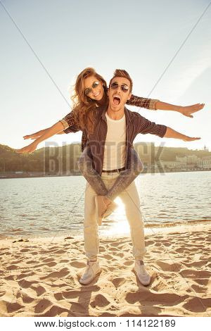 Happy Young Man Piggybacking His Girlfriend At The Seaside