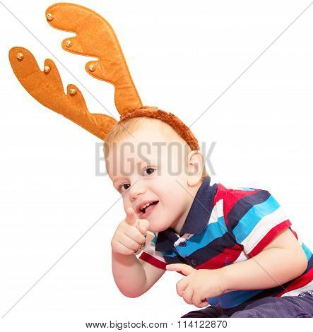 The Child, The Boy, With Deer Horns For A New Year's Masquerade On The Head, Bent And Points A Finge