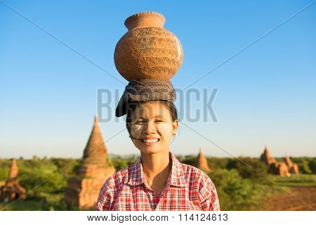 Portrait of Young Asian traditional female farmer carrying clay pot on head going back home, Bagan, Myanmar