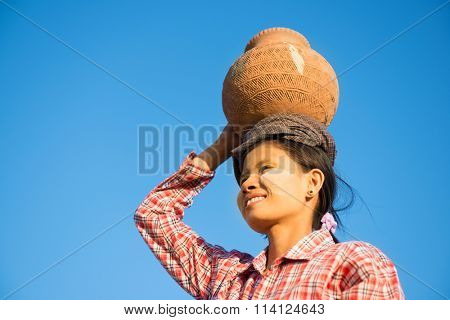Portrait of Young Asian Burmese traditional female farmer carrying clay pot on head going back home, Bagan, Myanmar