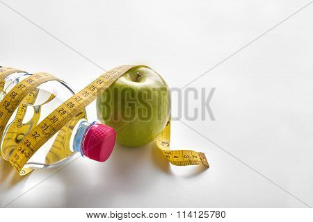 Measuring Tape Around A Bottle Of Mineral Water And Apple