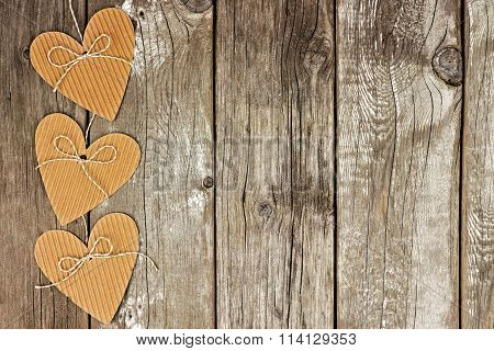 Side border of rustic heart shaped gift tags against wood